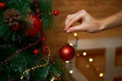 Flicka som hänger den dekorativa leksakbollen på xmas-träd Arkivfoto