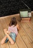 Flicka som håller ögonen på den gammala tv:n Royaltyfri Fotografi