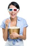 Flicka som håller ögonen på filmen 3D med popcorn Royaltyfria Foton