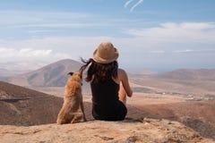 Flicka som håller ögonen på panoraman med hennes valphund royaltyfri fotografi