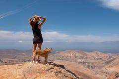 Flicka som håller ögonen på panoraman med hennes valphund royaltyfri bild