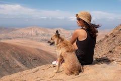 Flicka som håller ögonen på panoraman med hennes valphund arkivfoto