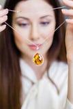 Flicka som håller halsbandet med gul safir Royaltyfri Fotografi