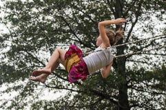 Flicka som högt svänger vid trädet Arkivfoton