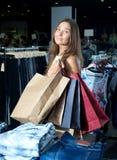 Flicka som har att shoppa pappers- påsar i händer Royaltyfri Foto