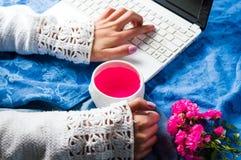Flicka som har en kopp te, medan arbeta royaltyfria bilder