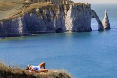 Flicka som har en vila nära klippan i Etretat Normandie Frankrike royaltyfria bilder
