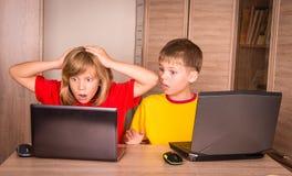 Flicka som har ett datorproblem Gulliga barn som använder bärbara datorer på H Royaltyfri Fotografi