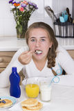 Flicka som har frukosten i kök Royaltyfri Bild