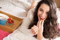 Flicka som har frukosten i säng Arkivbild