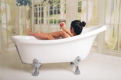 Flicka som har gyckel i bada Hon är i ett rymligt och elegant badrum arkivbild