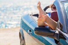 Flicka som har gyckel i blå cabriolet mot tonad himmelbakgrund Sommarsemester och loppbegrepp royaltyfri foto