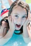 Flicka som har gyckel i pölen i det soliga vädret för sommar arkivbild