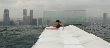 Flicka som har gyckel i pöl i Singapore Royaltyfri Bild