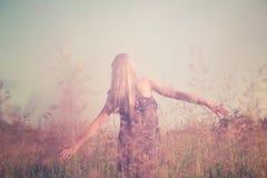 Flicka som har gyckel i sommarfält Arkivfoton