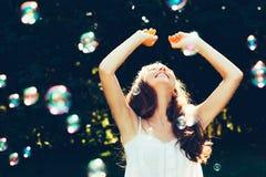 Flicka som har gyckel med bubblor royaltyfria bilder