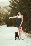 Flicka som har gyckel med hennes mopshund Arkivbild