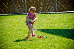 Flicka som har gyckel med spridaren i trädgård Arkivfoton