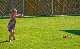 Flicka som har gyckel med spridaren i trädgård Royaltyfri Fotografi