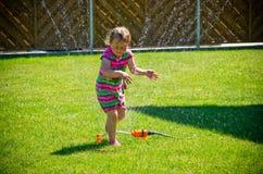 Flicka som har gyckel med spridaren i trädgård Arkivfoto