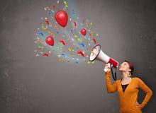 Flicka som har gyckel och att ropa in i megafonen med ballonger och konfettier Fotografering för Bildbyråer