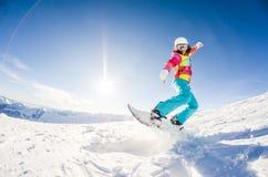 Flicka som har gyckel på hennes snowboard royaltyfri foto
