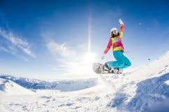 Flicka som har gyckel på hennes snowboard Royaltyfria Bilder