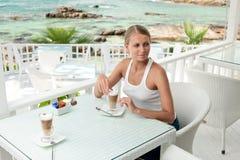 Flicka som har kaffestöt en havsiktscafe Arkivfoto
