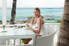 Flicka som har kaffestöt en havsiktscafe Royaltyfri Foto