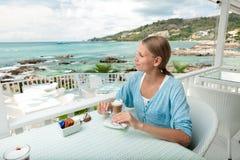 Flicka som har kaffestöt en havsiktscafe Royaltyfri Fotografi