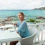 Flicka som har kaffestöt en havsiktscafe Arkivbild