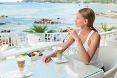 Flicka som har kaffestöt en havsiktscafe Arkivfoton