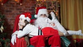 Flicka som har knäfalla för ben för gyckel vinkande liggande på Santa Claus sammanträde i en stol lager videofilmer