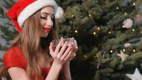 Flicka som har te nära julgranen lager videofilmer