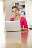 Flicka som hemma använder bärbar datordatoren Arkivfoton