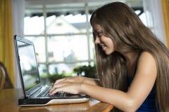 Flicka som hemma använder bärbar datordatoren Royaltyfria Bilder