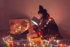 Flicka som hemma läser en bok under filten Arkivbilder