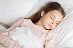 Flicka som hemma sover i säng arkivbilder
