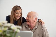 Flicka som hjälper till hennes farfar med datoren Arkivbild