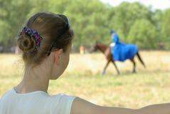 Flicka som håller ögonen på en häst Arkivbild