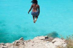 Flicka som hoppar av klippan i Curacao royaltyfria foton