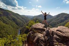 Flicka som hoppar på den höga steniga klippan med bergflodbakgrunden royaltyfria foton