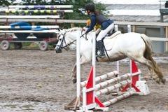 Flicka som hoppar till en competetion Royaltyfria Bilder
