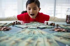Flicka som i regeringsställning ser valuta på skrivbordet arkivbilder