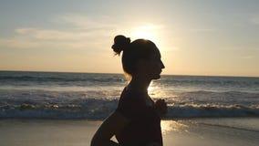 Flicka som joggar längs havkust under soluppgång Kontur av spring för ung kvinna på havsstranden på solnedgången kvinnlig lager videofilmer