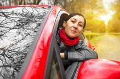 Flicka som kör en röd bil arkivbild