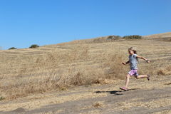 Flicka som kör i smutsfält Arkivbilder