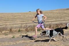 Flicka som kör med hunden Arkivfoto