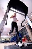 Flicka som kör på treadmillen i idrottshallen Royaltyfria Bilder