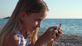 flicka som 4K spelar minnestavlan på stranden, solnedgångsikt, barn som använder den smarta telefonen, kustlinje stock video